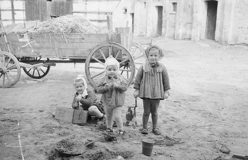 Dziewczynki na podwórku przy wozie, od lewej: Halinka Wacławowicz, Tereska i Alinka Czyżowicz, Głębowice, Dolny Śląsk, koniec lat 50. XX w.